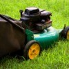 Green lawnmower with yellow wheels on grass.
