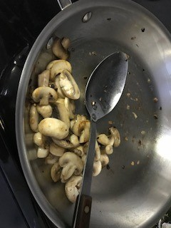 adding sliced mushrooms to skillet