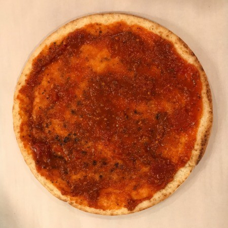 Store-bought pizza crust with tomato sauce.