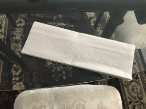 A folded white paper towel before being used.