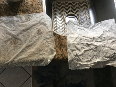 Two paper towels, spread out and drying on the counter and sink area.