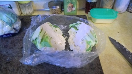 A bag that contains a head of cauliflower from the grocery store, cut in half.