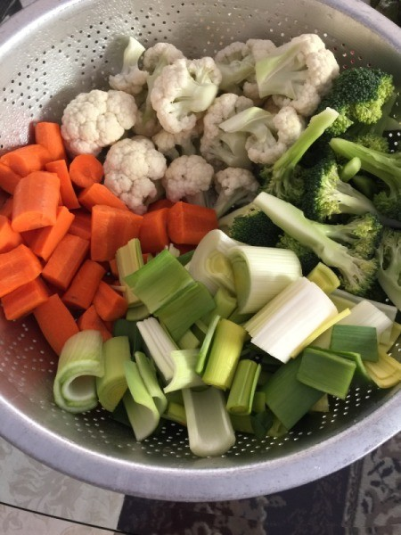 cut leeks, carrots, cauliflower and broccoli in colander