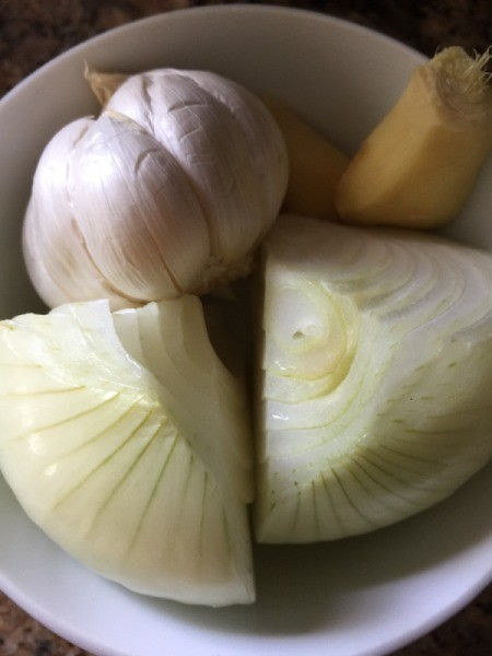 onion, quartered and garlic and ginger in bowl
