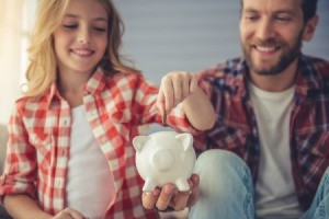 Father Helping Daughter Put Money in Piggy Bank