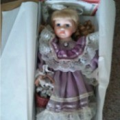 Value of a Porcelain Doll - doll wearing a lavender dress in box