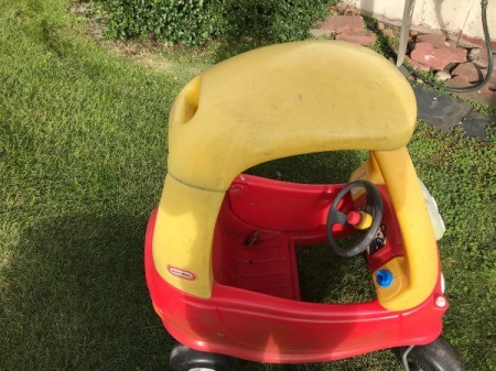 A colorful plastic car for children, found on the curb.