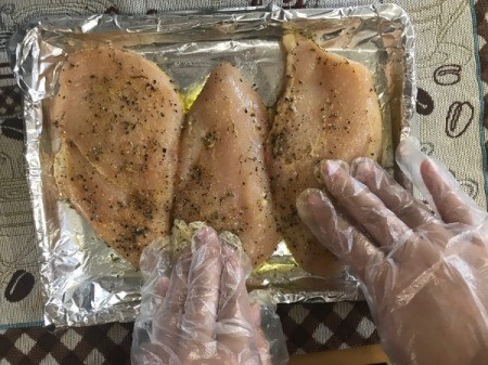 gloved hands seasoning chicken Breasts