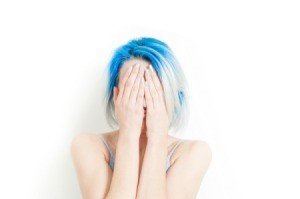 Woman with blue hair covering her face with her hands.