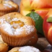 Peach muffins sprinkled with powdered sugar.