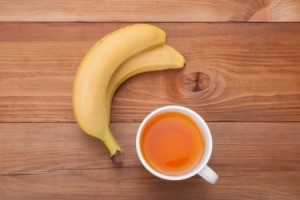 Banana and Tea on a wood surface.