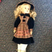 Identifying Porcelain Dolls - blonde doll with plaid apron over dark dress with matching hat