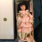 Value of Heritage House Musical Doll - doll wearing pink ruffle dress in a box