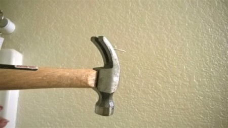 A hammer claw being used upside down to remove a nail from the wall.