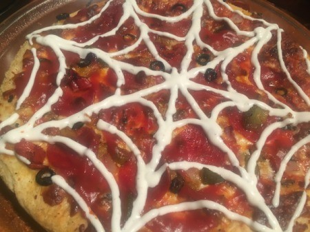 A spooky spider pizza, decorated with a ranch web.