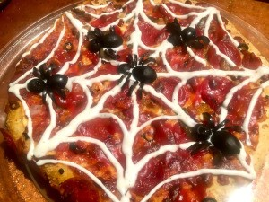 A spooky spider pizza, decorated with spider olives and a ranch web.