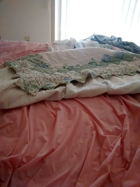 A bed in the process of having the sheets changed.