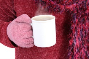 Gloved Hand Holding Mug of Hot Chocolate