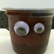 A chocolate pudding cup with bat wings and eyes.