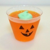 An orange cup of Jello with a Jack-o'-Lantern face.