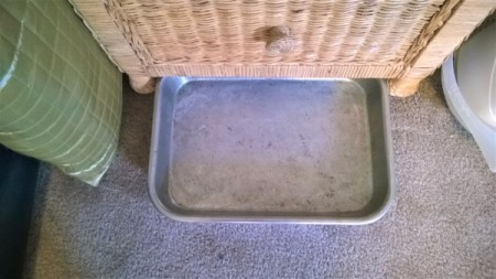 A baking tray next to a nightstand.
