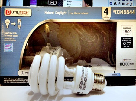 A package of CFL bulbs with a loose bulb next to it.