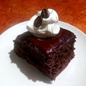 Coffee Crunch Chocolate Cake with whipped cream on plate