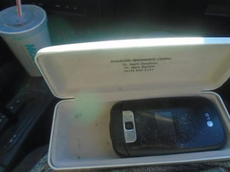 An eyeglass case that is holding a cell phone.