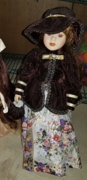 Identifying a Porcelain Doll - doll wearing a dark jacket and matching hat over a floral skirt