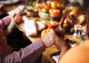 A group of people holding hands around a Thanksgiving dinner table.