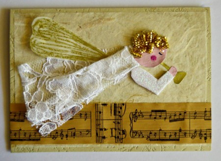 Angel Blowing On Trumpet Christmas Card - cut wing from waxed paper, add gold details and glue narrow end in place, use 3-D foam squares for other end