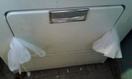 Drying Shoes Without the Banging - ends of mesh bag protruding from dryer door