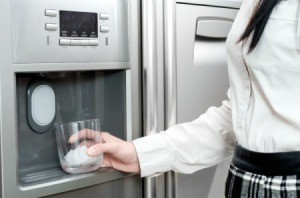 Woman Getting Ice From Refrigerator