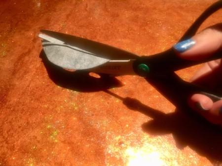 Scissors cutting through fine sandpaper to sharpen them.