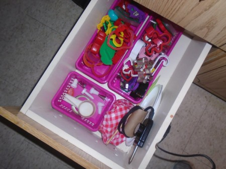 A drawer organized with small containers.