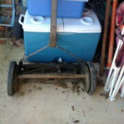 Value of an Old Reel Mower - mower leaning on a stack of coolers