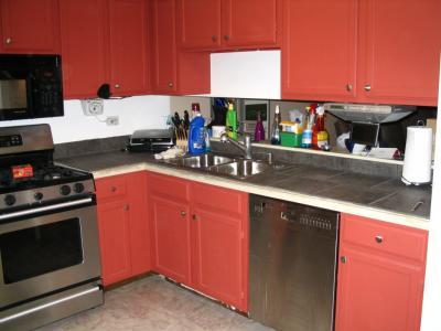 A tiled kitchen counter with red cabinets.