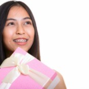 Close up of thoughtful young happy Asian teenage girl smiling while holding gift box