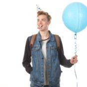 Teenage boy with birthday hat holding a blue balloon.