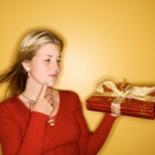 A girl looks at a wrapped present