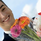 Happy man holding flowers and gift.