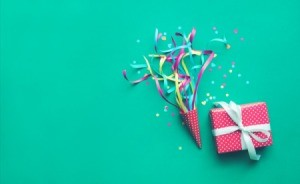 Colorful confetti, streamers and gift box on green color