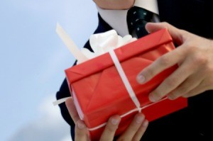 man holding gift in red box with white ribbon outdoors, close-up