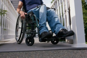 Man in a wheelchair on the top of home access ramp