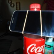 A soda bottle and rubber band being used as a phone stand.