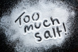 """Too Much Salt"" written in salt on black table."