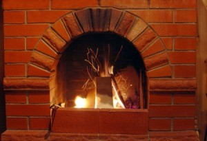 Fire in a brick fireplace with soot on the outside.