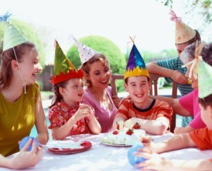 Group of kids with party hats sitting at a table.