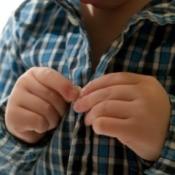 Child Buttoning Shirt