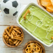 Soccer field dip, soccer ball and snacks on table.